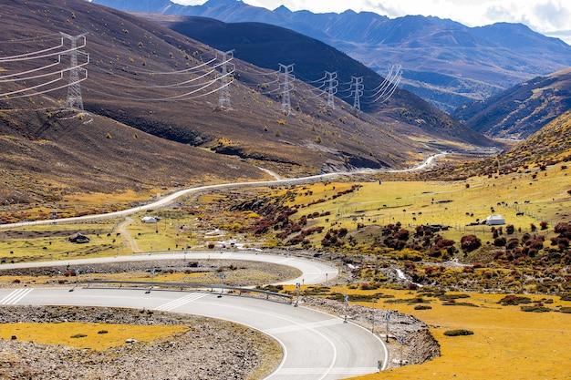 Kleurrijk landschap met prachtige bergweg met een perfect asfalt hoge rotsen blauwe hemel bij zonsopgang in de zomer
