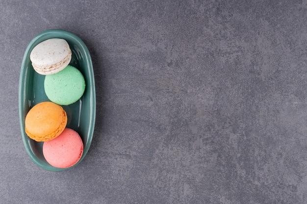 Kleurrijk macaronsdessert dat op een steenlijst wordt geplaatst.