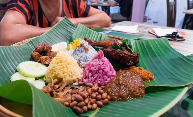 Kleurrijk nasi lemak of traditioneel voedsel van maleisië in groen banaanblad op lijst bij restaura