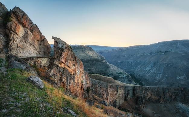 Kleurrijk ochtendlandschap met silhouetten van grote rotsachtige bergen en epische diepe kloof. onverharde bergweg, serpentijn met een klif en een prachtig panoramisch uitzicht op de kloof.