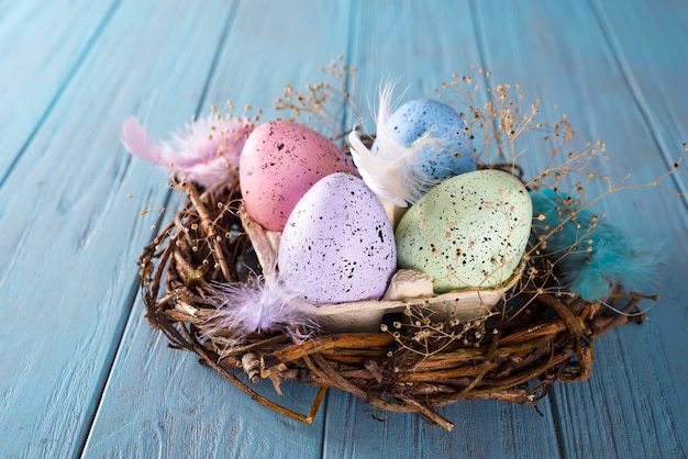 Kleurrijk paasei in het nest op houten achtergrond