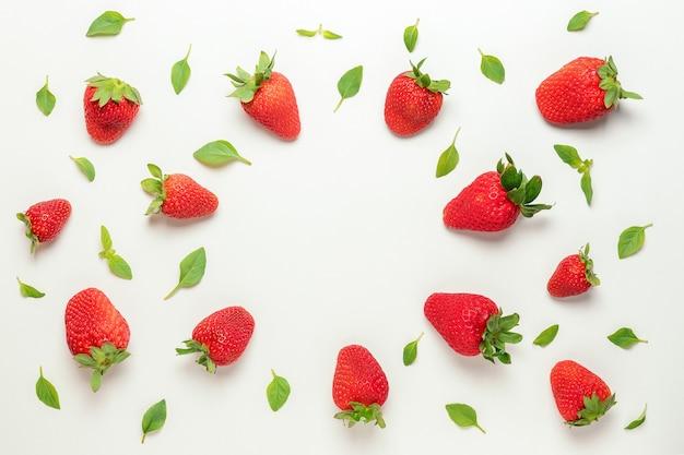 Kleurrijk patroon gemaakt van aardbeien en groene bladeren.