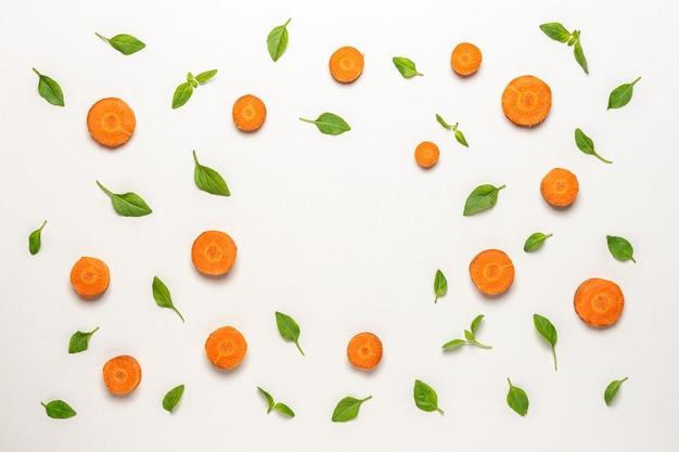 Kleurrijk patroon gemaakt van gesneden wortelen en basilicum groene bladeren.