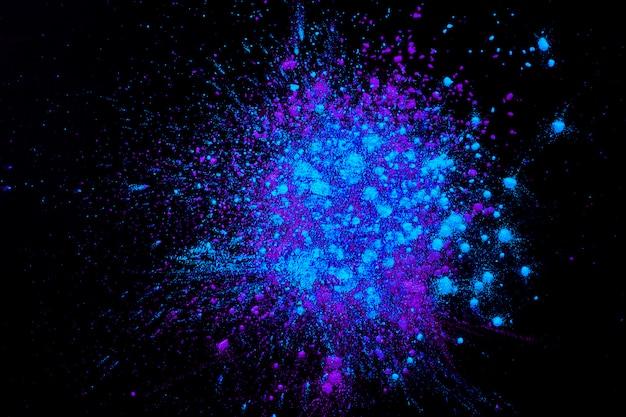 Kleurrijk poeder gemengd op een donkere ondergrond