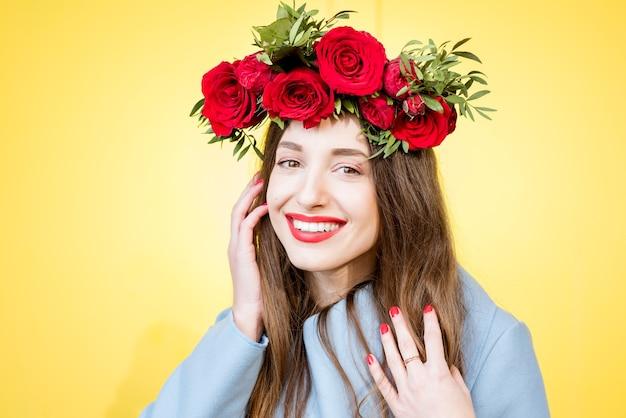 Kleurrijk portret van een mooie vrouw in blauwe jas met krans gemaakt van rode rozen op de gele achtergrond