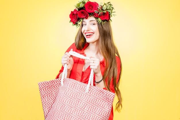Kleurrijk portret van een mooie vrouw in een rode jurk met een krans gemaakt van rode rozen die met een boodschappentas op de gele achtergrond staat. lente winkelconcept