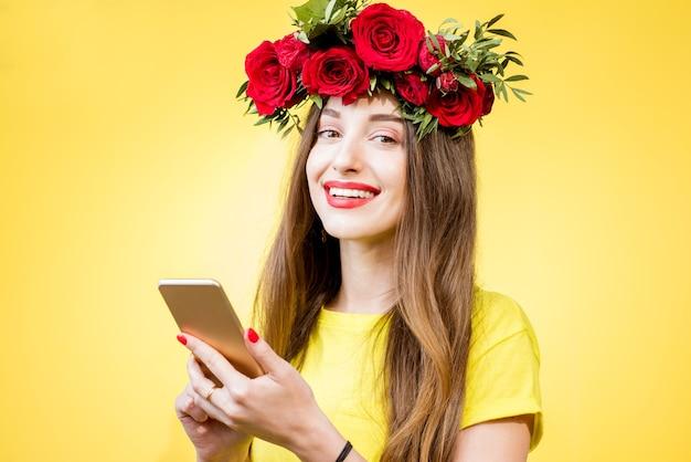 Kleurrijk portret van een mooie vrouw in geel t-shirt met krans gemaakt van rode rozen met behulp van telefoon op de gele achtergrond