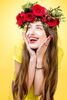 Kleurrijk portret van een mooie vrouw in geel t-shirt met krans gemaakt van rode rozen op de gele achtergrond