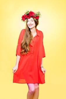 Kleurrijk portret van een mooie vrouw in rode jurk met krans gemaakt van rode rozen op de gele achtergrond