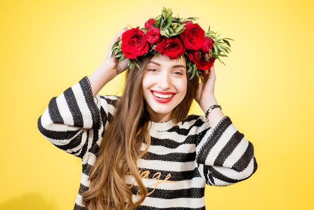 Kleurrijk portret van een mooie vrouw in trui met krans gemaakt van rode rozen op de gele achtergrond
