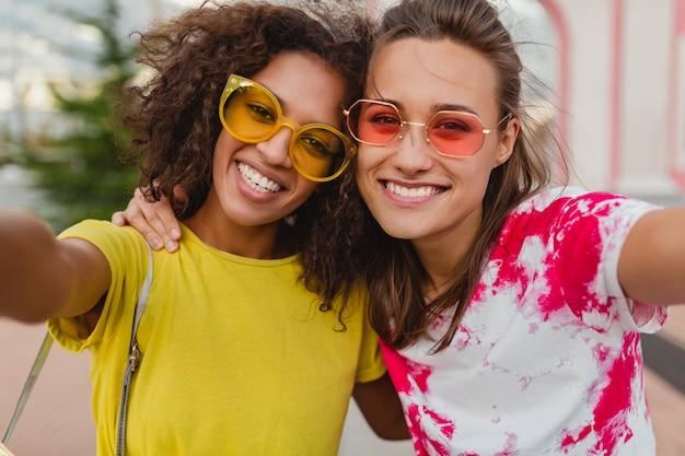 Kleurrijk portret van gelukkige jonge meisjesvrienden die zittend in straat selfie foto nemen op mobiele telefoon, vrouwen die samen pret hebben
