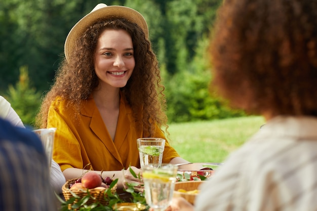Kleurrijk portret van lachende jonge vrouw genieten van diner met vrienden buiten zittend aan tafel tijdens zomerfeest