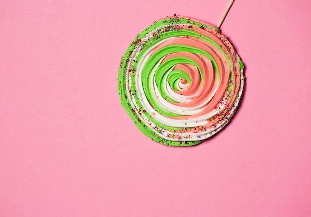 Kleurrijk schuimgebakje op stok op kleurrijke achtergrond.
