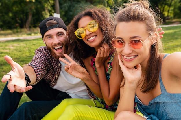 Kleurrijk stijlvol gelukkig jong gezelschap van vrienden zitten park, man en vrouw samen plezier