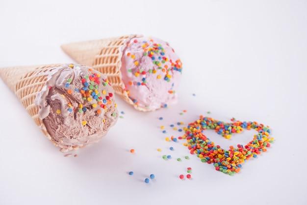 Kleurrijk suikergoed in de vorm van een hart en roomijskegels op wit