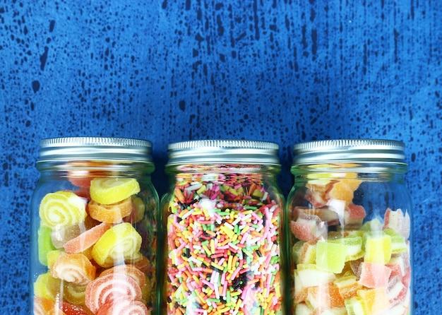 Kleurrijk suikergoed op houten lijst blauwe achtergrond.