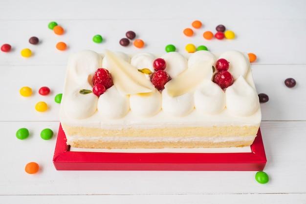 Kleurrijk suikergoed rond de cake op houten lijst