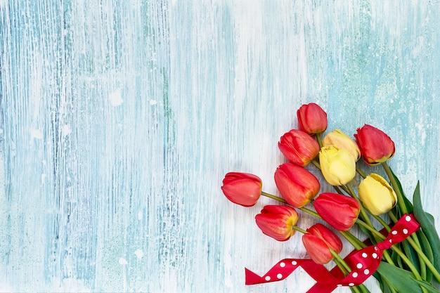 Kleurrijk tulpenboeket dat met rood lint op blauwe houten achtergrond wordt verfraaid
