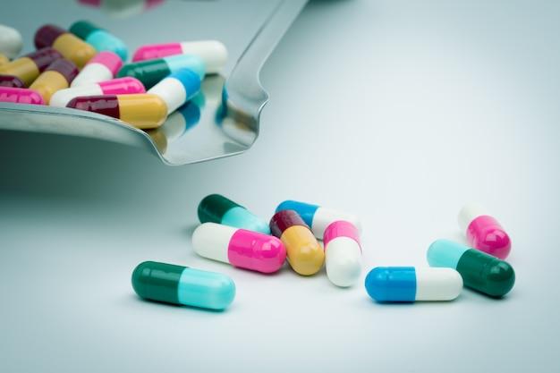 Kleurrijk van antibiotische capsulespillen op dienblad van het roestvrij staaldrug, drugweerstand