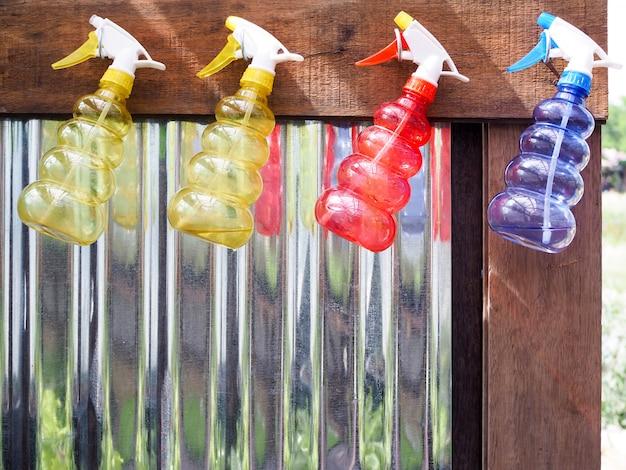 Kleurrijk van de fles van de waternevel het hangen op houten muur in tuin met zinkoppervlakte.