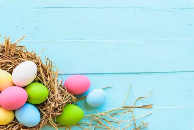 Kleurrijk van paaseieren in nest op houten achtergrond.