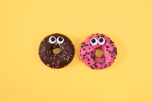 Kleurrijk verglaasd donuts met grappige ogen op gele achtergrond.