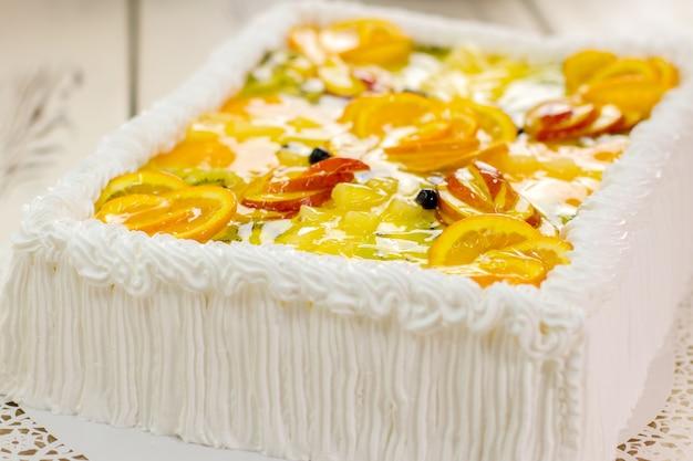 Kleurrijk versierde taart. stukjes fruit en gelei. dessert met roomboter. op maat gemaakte taart in restaurant.