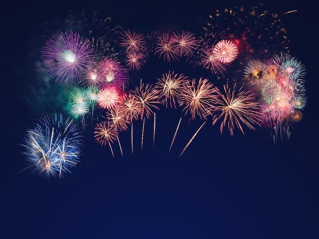Kleurrijk vuurwerk op de zwarte hemelachtergrond met vrije ruimte voor tekst