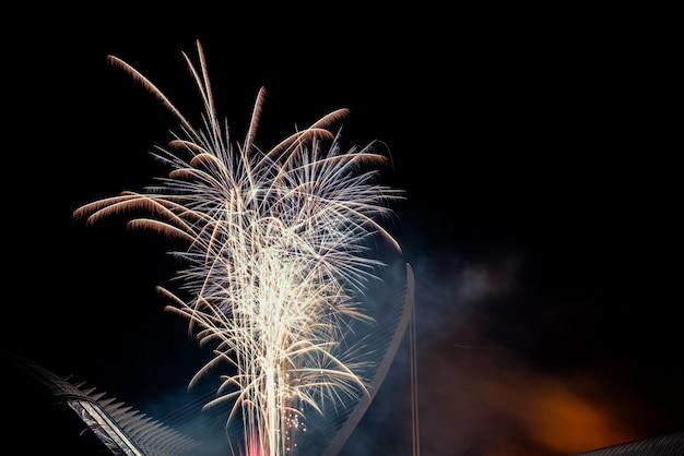 Kleurrijk vuurwerk over de nachtstad, vrije zwarte ruimte voor tekst.