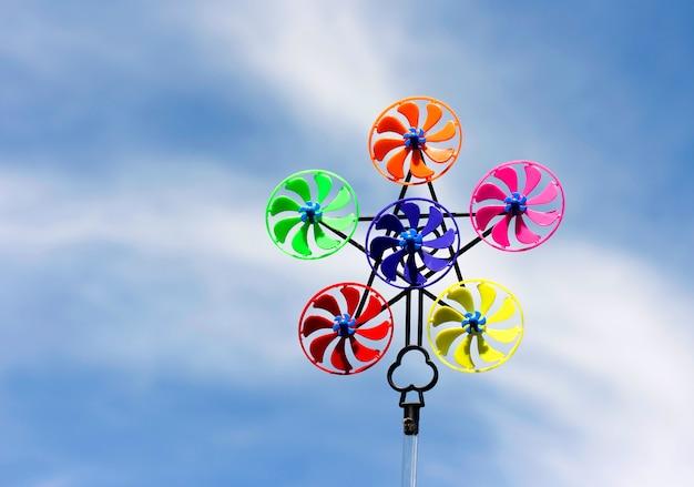 Kleurrijk windmolenspeelgoed op blauwe hemel