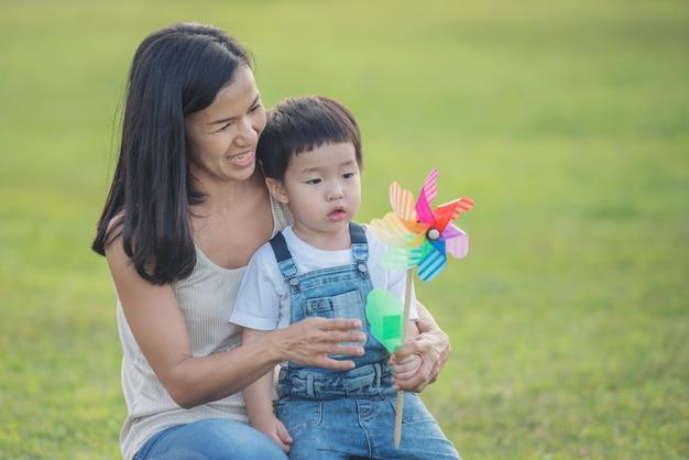 Kleurrijk windmolenspeelgoed voor kinderen. lachend kind dat graag speelt. kleine jongen blaast tegen een kleurrijke windmolen in de zomer op zomerkamp. vrouw en kleine jongen spelen.