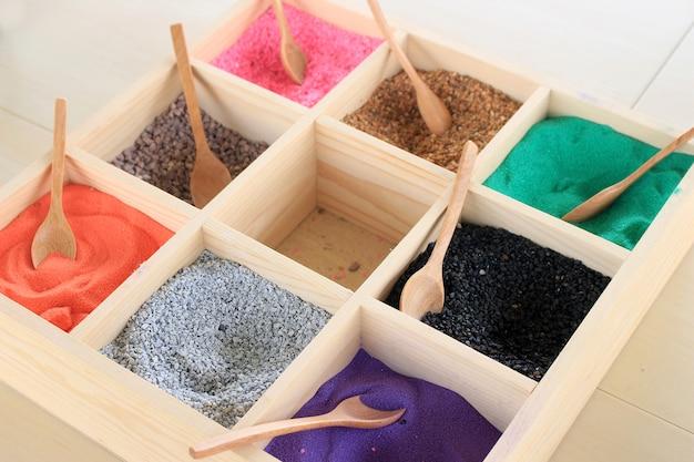 Kleurrijk zand in houten doos