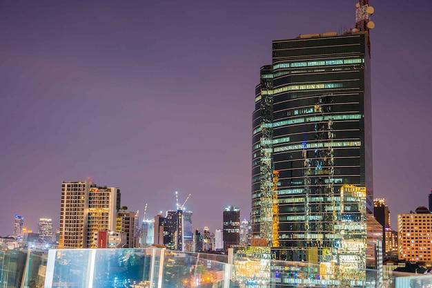 Kleurrijke abstracte foto wazig van stad moderne gebouwen nacht bangkok stadsgezicht uitzicht op schemering tijd, versierd met de-focus bokeh steden kantoren van reflecterend gebouw in bangkok thailand.