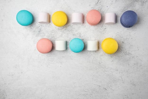 Kleurrijke amandel macarons op witte achtergrond met marshmallows.