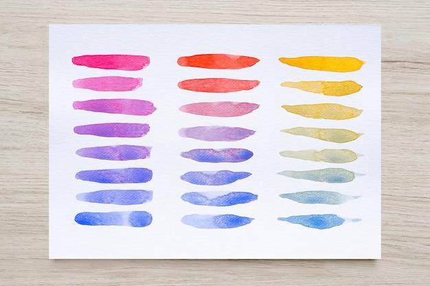 Kleurrijke aquarel vlekken op wit papier met houten achtergrond. set aquarel borstel strepen. inktstreken. platte soort penseelstreek. detailopname.