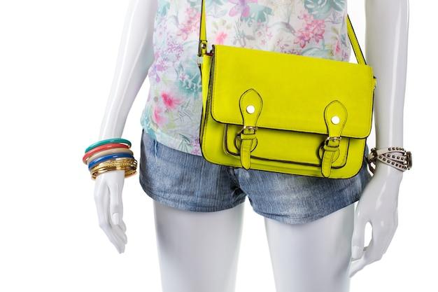 Kleurrijke armbanden en limoen portemonnee. de kleurrijke accessoires van de vrouw op etalagepop. elementen van de zomeroutfit voor meisjes. speciale aanbieding bij kledingwinkel.