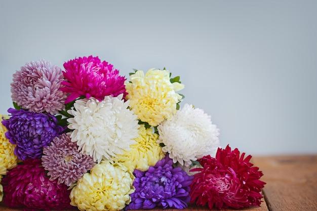 Kleurrijke asterbloemen op houten achtergrond. callistephus chinen