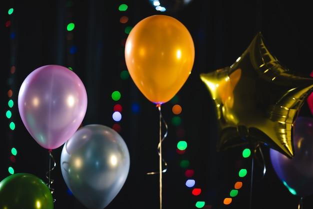 Kleurrijke ballondecoratie voor feest, viering oudejaarsavond. kerstfeest, ballon op zwarte achtergrond, heliumballonnen, oranje groen blauw en paars.