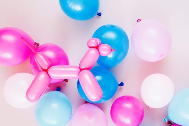 Kleurrijke ballonnen en ballonhonden op pastelkleurige achtergrond. feestelijk of verjaardagsfeestje concept. plat lag, bovenaanzicht.