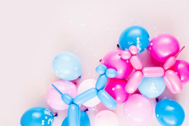 Kleurrijke ballonnen en ballonhonden op pastelroze achtergrond. feestelijk of verjaardagsfeestje concept. plat lag, bovenaanzicht.