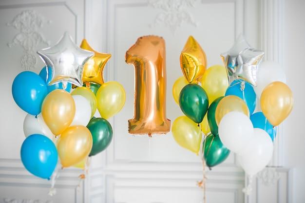 Kleurrijke ballonnen en folie grote gouden nummer één in een witte kamer