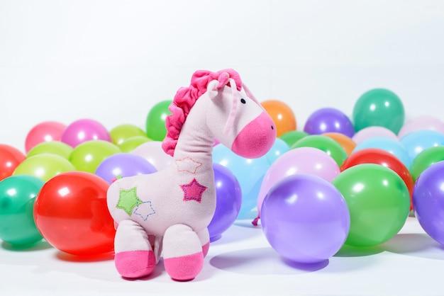 Kleurrijke ballonnen en roze knuffel op een lichte ondergrond