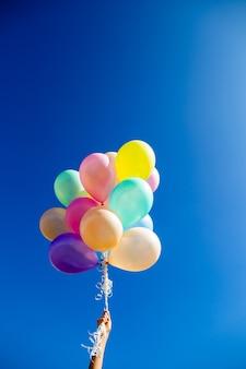 Kleurrijke ballonnen in de hand gehouden tegen blauwe hemel