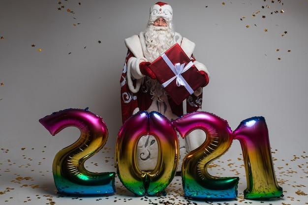 Kleurrijke ballonnen in de vorm van 2021 en de kerstman met cadeau om kerstmis en nieuwjaar te vieren