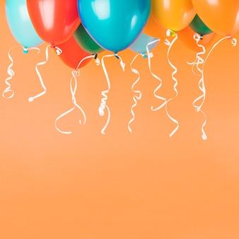 Kleurrijke ballonnen met linten op oranje achtergrond met kopie ruimte