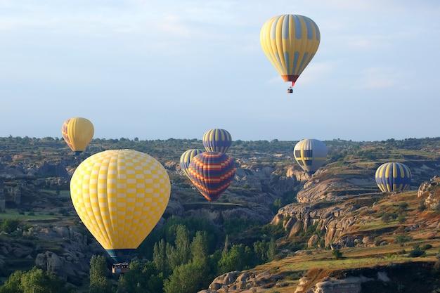 Kleurrijke ballonnen met mensen vliegen in de vallei in cappadocië