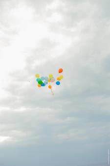 Kleurrijke ballonnen vliegen in de lucht. veelkleurige ballonnen in een bundel tegen de hemel.