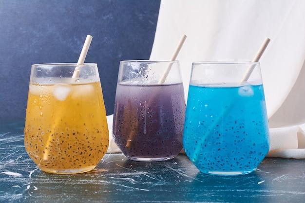 Kleurrijke bessen met een kopje drank op blauw.
