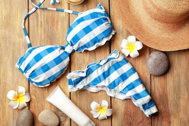 Kleurrijke bikini, bloemen en hoed op houten oppervlak