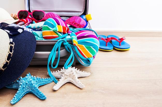 Kleurrijke bikini en kleding in bagage op de laminaatvloer